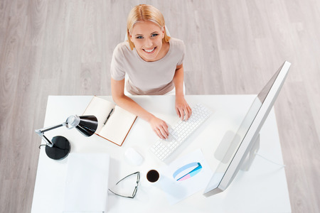 lifestyle woman: Businesswoman at working place. Top view of beautiful young blond hair woman working at the computer and looking at camera while sitting at her working place