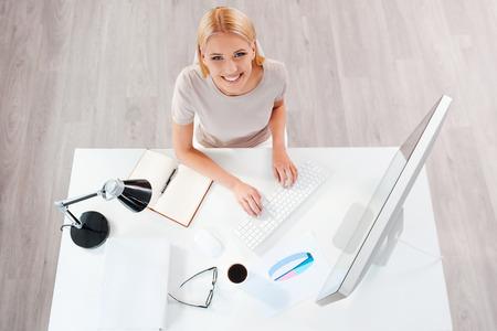 femme blonde: D'affaires au lieu de travail. Vue du haut de la belle jeune femme de cheveux blonds travaillant � l'ordinateur et en regardant la cam�ra assis � son lieu de travail