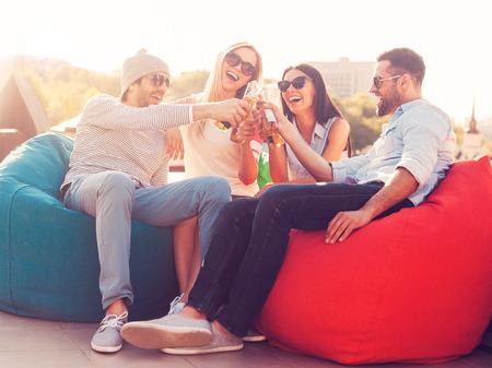 saúde: Elogios a nós! Quatro jovens alegres que cheering com cerveja e sorrindo, sentado com os sacos de feijão no telhado do edifício