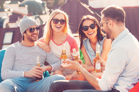 Roof party. Four young cheerful people chatting and drinking beer while sitting at the bean bags on the roof of the building Stock Photo