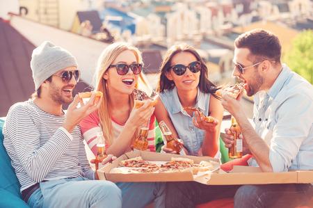 Freunde und Pizza. Vier junge fröhliche Menschen essen Pizza und Bier trinken während der Sitzung an den Sitzsäcken auf dem Dach des Gebäudes Standard-Bild - 39500600