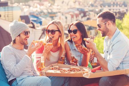 Pizza Zeit. Vier junge glückliche Leute, die Pizza essen und Bier trinken während der Sitzung an den Sitzsäcken auf dem Dach des Gebäudes Standard-Bild