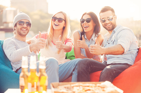 Enjoying good time. Four young cheerful people showing their thumbs up and smiling while sitting on bean bags at the outdoors terrace with pizza and beer laying on foreground