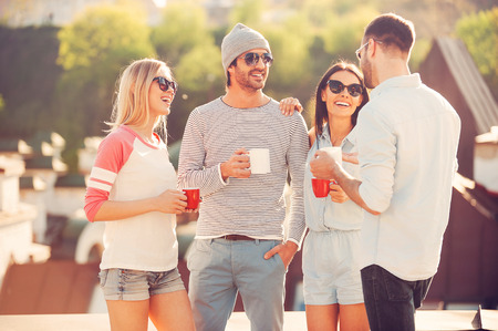 Koffiepauze. Vier jonge vrolijke mensen praten en koffie te drinken terwijl je op het dakterras bij elkaar Stockfoto