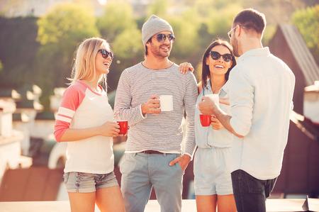 persona de pie: Pausa para el café. Cuatro personas alegres jóvenes charlando y bebiendo café mientras está de pie en la terraza junto