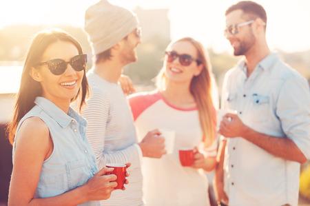 alimentos y bebidas: Disfrutar de descanso para tomar café. Mujer joven hermosa que sostiene la taza de café y sonriendo mientras está de pie junto a sus amigos en la terraza de la azotea
