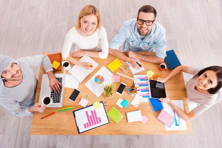 creative: Successful creative team. Top view of group of business people in smart casual wear working together and smiling while sitting at the wooden desk