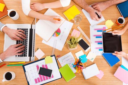 창조적 인 작업 과정. 나무 책상에 앉아있는 동안 함께 일하는 사람들의 상위 뷰 확대 이미지 스톡 콘텐츠