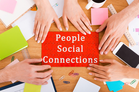 connection connections: People social connections. Top view close-up image of people touching jigsaw puzzle with social connection text on it