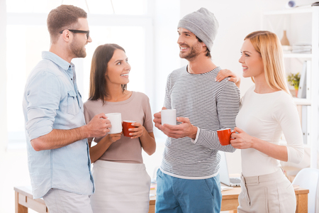 break: Coffee break chat. Group of business people in smart casual wear holding coffee cups and smiling while standing close to each other in office