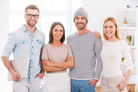 work group: The best creative team. Group of business people in smart casual wear holding coffee cups and smiling while standing close to each other in office Stock Photo