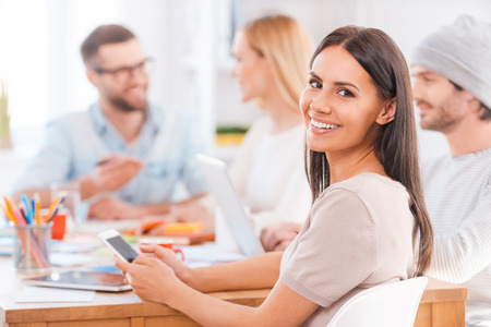 woman working out: Feeling confident in her team. Beautiful young woman looking over shoulder and smiling while holding mobile phone and sitting together with his colleagues at the wooden table in office