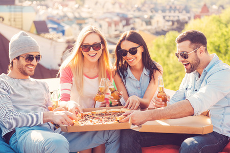 Enjoying pizza with friends. Four young cheerful people eating pizza and drinking beer while sitting at the bean bags on the roof of the building