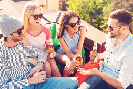 man outdoors: Carefree talk with friends. Top view of four young cheerful people chatting and drinking beer while sitting at the bean bags on the roof of the building