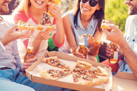 Pizza time! Close-up of four young cheerful people eating pizza and drinking beer outdoors