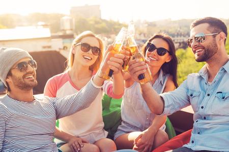 celebração: Amigos e cerveja. Quatro jovens alegres que cheering com cerveja e sorrindo, sentado com os sacos de feij