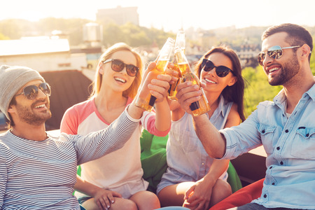 Friends and beer. Four young cheerful people cheering with beer and smiling while sitting at the bean bags on the roof of the building Stockfoto