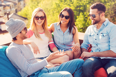 adult male: Trascorrere grande momento con gli amici. Vista dall'alto di quattro giovani allegri chat mentre seduti ai sacchi di fagioli sul tetto del palazzo