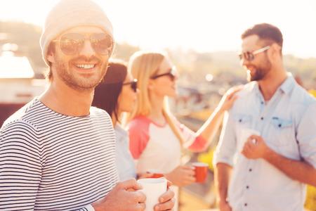personas de pie: Hora del caf�. Apuesto joven en el sombrero que sostiene la taza de caf� y sonriendo mientras est� de pie junto a sus amigos en la terraza de la azotea