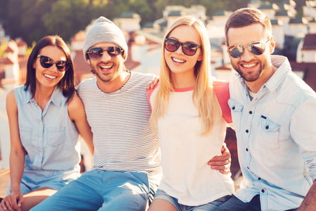 hug: We are the best friends! Four young cheerful people bonding to each other and smiling while sitting on the roof of the building together Stock Photo