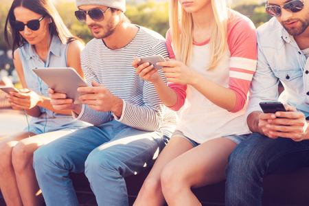 čtyři lidé: Kultura mládeže. Čtyři mladí lidé sedí blízko u sebe a při pohledu na jejich gadgets