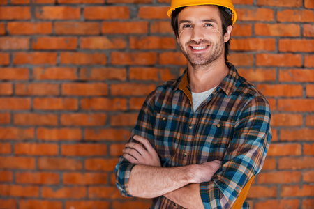 Planning a new construction. Smiling young man in hardhat keeping arms crossed and looking at camera while standing against brick wall