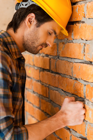closed fist: Carpenter in despair. Side view of depressed young man in hardhat leaning at the brick wall and keeping eyes closed Stock Photo