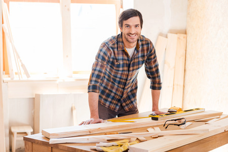 carpentry: Smiling woodworker. Cheerful young male carpenter leaning at the wooden table with diverse working tools laying on it