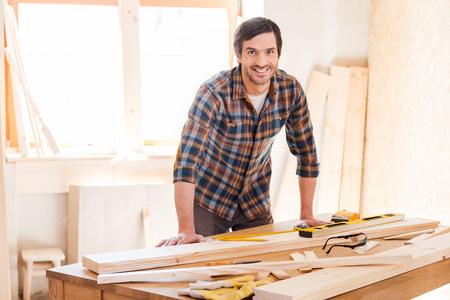 herramientas de carpinteria: Sonriente trabajador de la madera. Carpintero masculino joven alegre que se inclina en la mesa de madera con diversas herramientas de trabajo que pone en ella