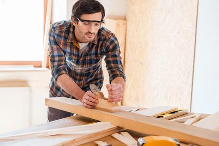 木材加工。自信を持って若い男性大工彼のワーク ショップで木材での作業