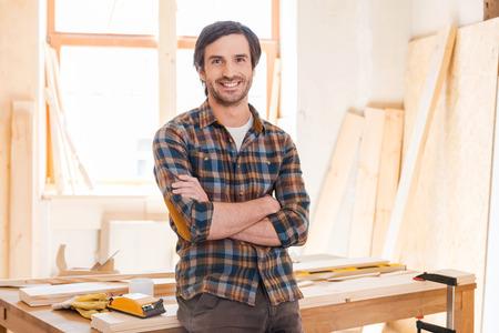 carpintero: Mi taller es mi mundo! Feliz joven carpintero masculina manteniendo los brazos cruzados y apoyado en la mesa de madera con diversas herramientas de trabajo que pone en ella