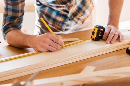 Exact medido. Primer plano de joven carpintero masculino realizar mediciones en el tablón de madera Foto de archivo - 39501575
