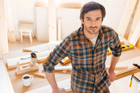 man only: Master of his trade. Top View of confident young male carpenter leaning at the wooden table with diverse working tools laying on it Stock Photo