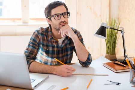 pensando: À espera de inspiração. Homem novo pensativo que prende a mão no queixo e olhando para longe, sentado em seu lugar de trabalho