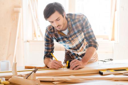 wood: Precyzja w całym. Poważny młody mężczyzna pracy stolarza z drewna w swoim warsztacie