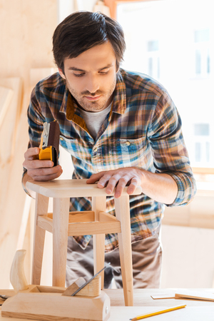 Working with wood is his passion. Concentrated young male carpenter working in his workshop