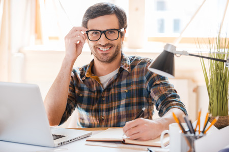 man writing: Ready for productive work. Smiling young man writing in note pad and adjusting his eyewear while sitting at his working place
