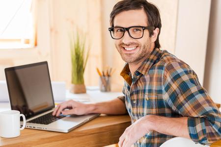Grande humor para bom trabalho. Homem novo considerável que trabalha em seu laptop e olhando a câmera sobre os ombros enquanto está sentado em seu lugar de trabalho