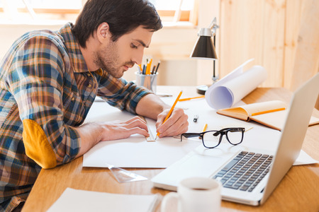 Getting to the point. Side view of concentrated young man working while sitting at his working place