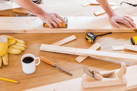 carpintero: Herramientas de trabajo para el carpintero. Primer plano de carpintero masculino para trabajar en la mesa de madera con diversas herramientas de trabajo que pone en ella
