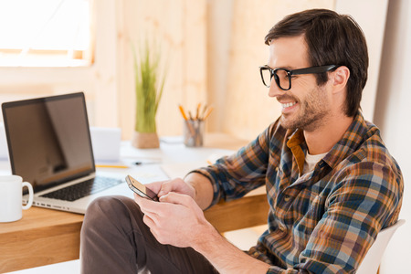 always: My smart phone is always at hand. Cheerful young man holding mobile phone and typing message while sitting at his working place