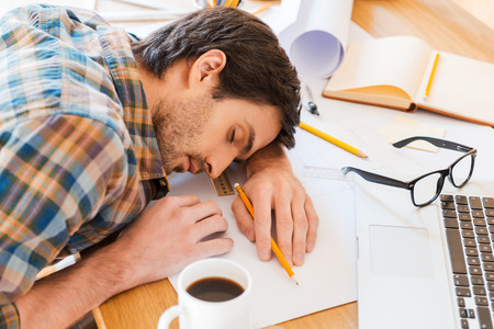 working place: Feeling exhausted. Top view of young man sleeping while sitting at his working place Stock Photo
