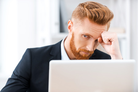 one mature man only: Failed again. Frustrated bearded businessman working on laptop and touching his head while sitting at his working place Stock Photo