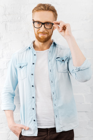 looking good: Looking good. Confident young bearded man adjusting his eyewear and looking at camera while standing against brick wall Stock Photo
