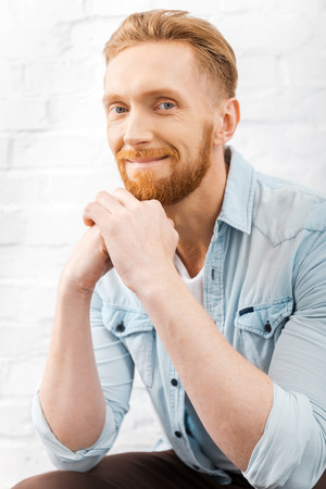 chin on hands: He is got a charming personality. Cheerful bearded man holding hands on chin and looking at camera while sitting against brick wall