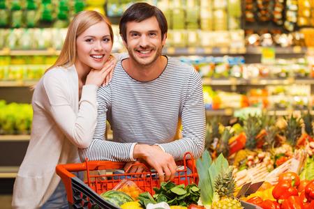 tiendas de comida: Juntos de compras para la cena. Alegre joven pareja sonriendo a la cámara y de pie detrás de su carrito de compras en una tienda de alimentos