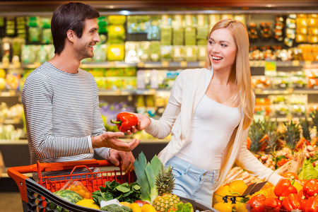 woman shopping cart: Shopping is a fun. Happy young women giving red pepper to her boyfriend while shopping in a food store