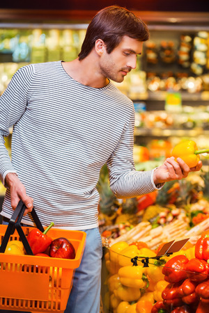 freshest: Only the freshest veggies. Handsome young men holding pepper and shopping bag while standing in a food store Stock Photo