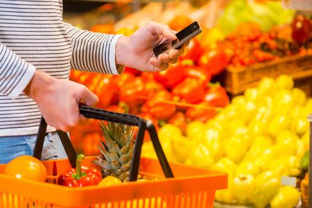 시도 모두를 구입하는 것을 잊지 않도록. 식품 매장에 서있는 동안 젊은 남자의 근접 쇼핑 가방과 휴대 전화를 들고