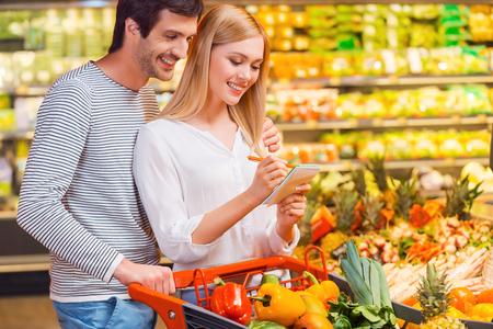 Kiezen alleen gezonde voeding. Gelukkig jong koppel binding aan elkaar en glimlachen tijdens het winkelen in een supermarkt